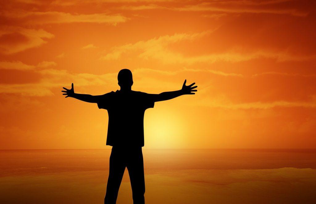 Mensch der die Arme ausstreckt Richtung Sonnenuntergang