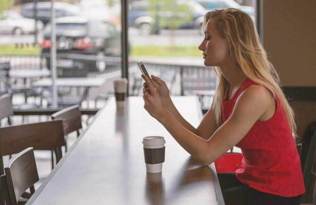 Frau sitzt in einem Café am Handy